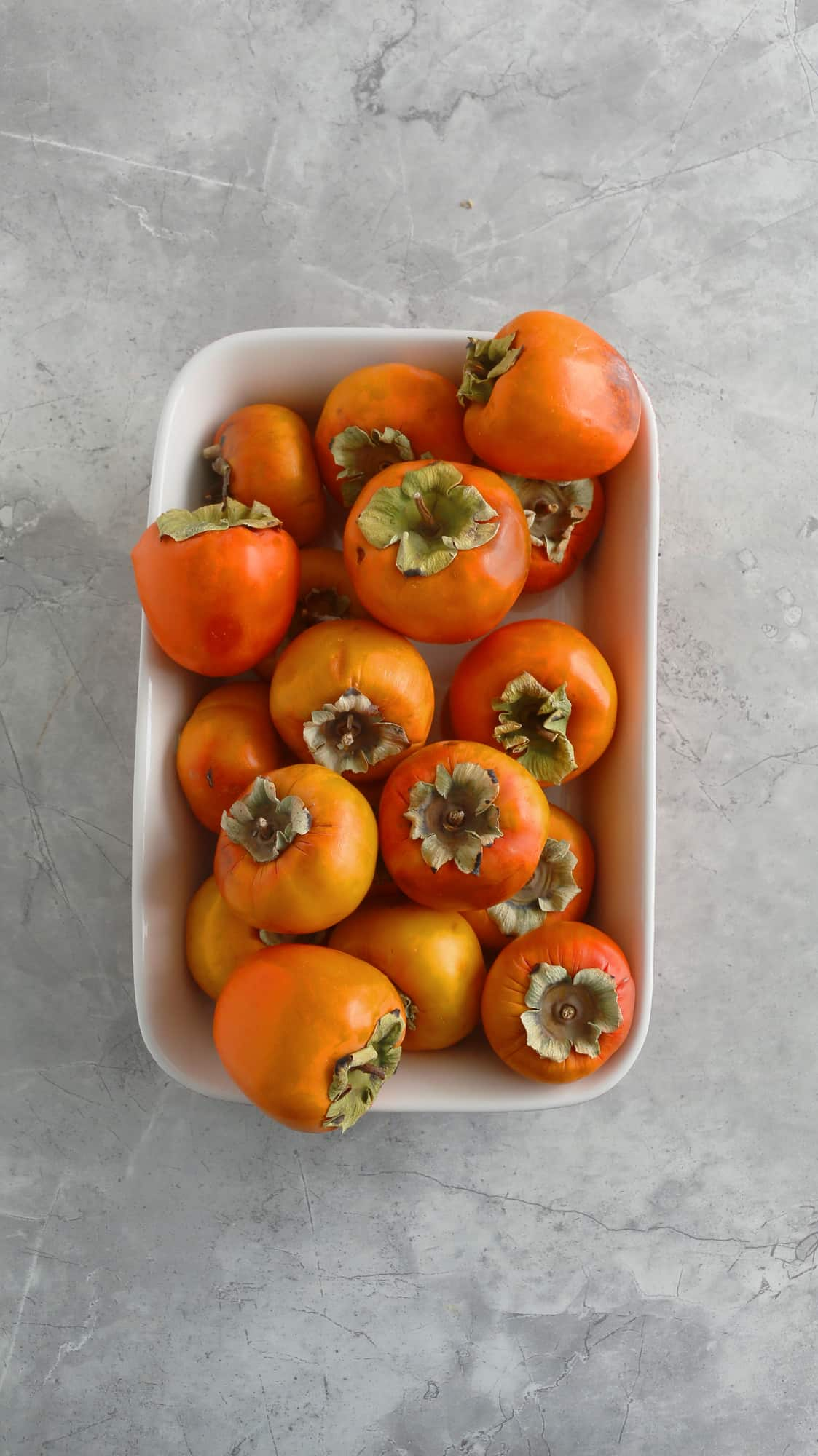 fuyu persimmons on a rectangle caserole dish