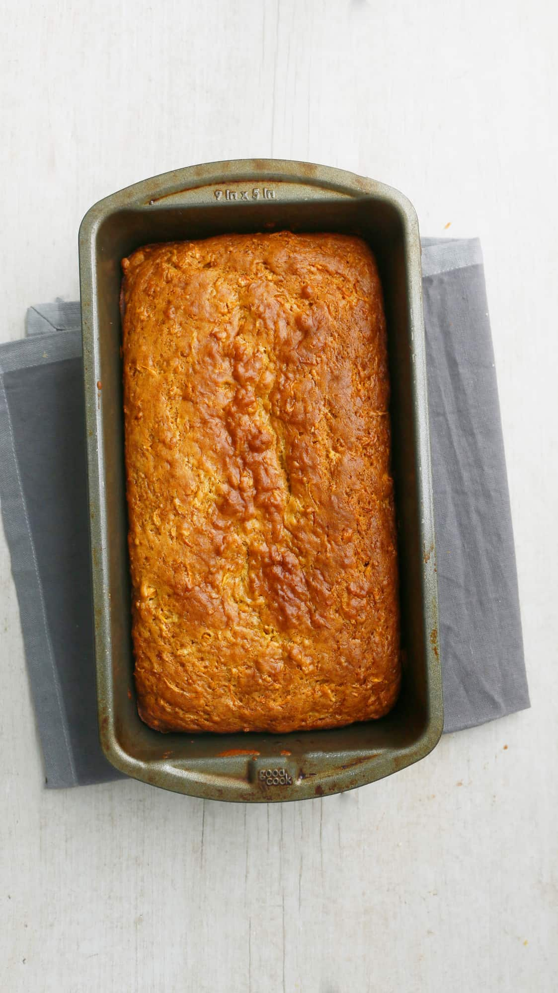 baked loaf of persimmon bread placed on a grey napkin