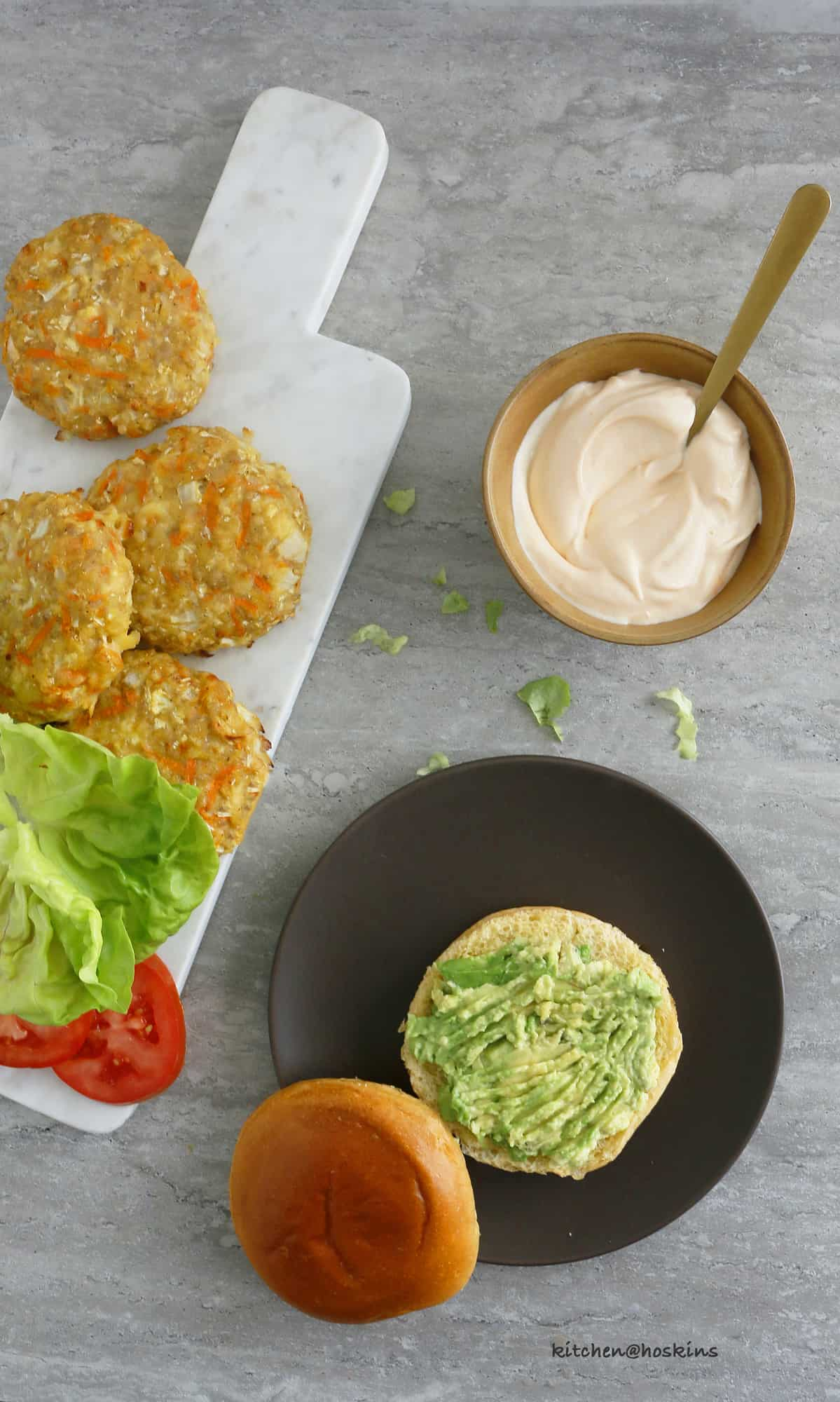 healthy chicken burger patties, mashed avocado, lettuce, tomato and sriracha mayo ready to assembled.