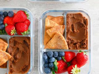 glass containers with sweet hummus, strawberries and pita chips.