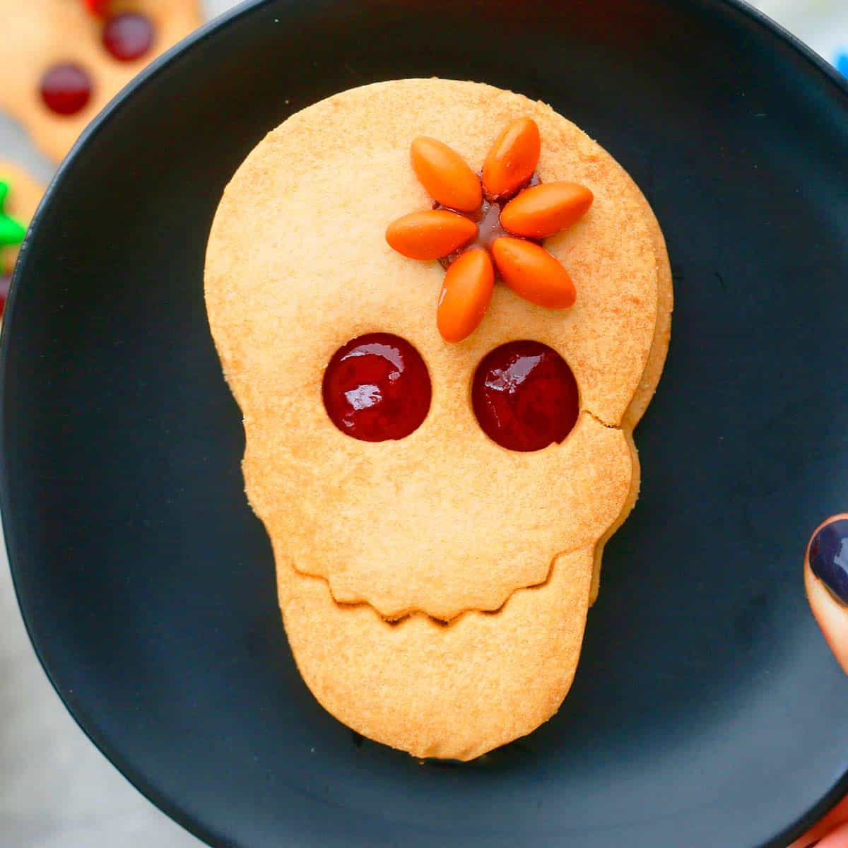 decorated halloween skull cookies on a plate