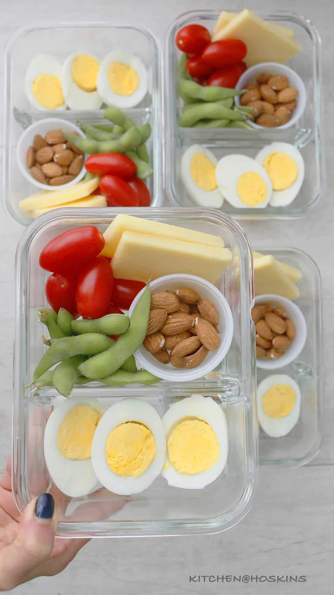 boiled eggs, cheese, almonds, edamame and tomatoes in bento box