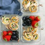 turkey apple and cheddar pinwheels, strawberries, grapes in a lunch box