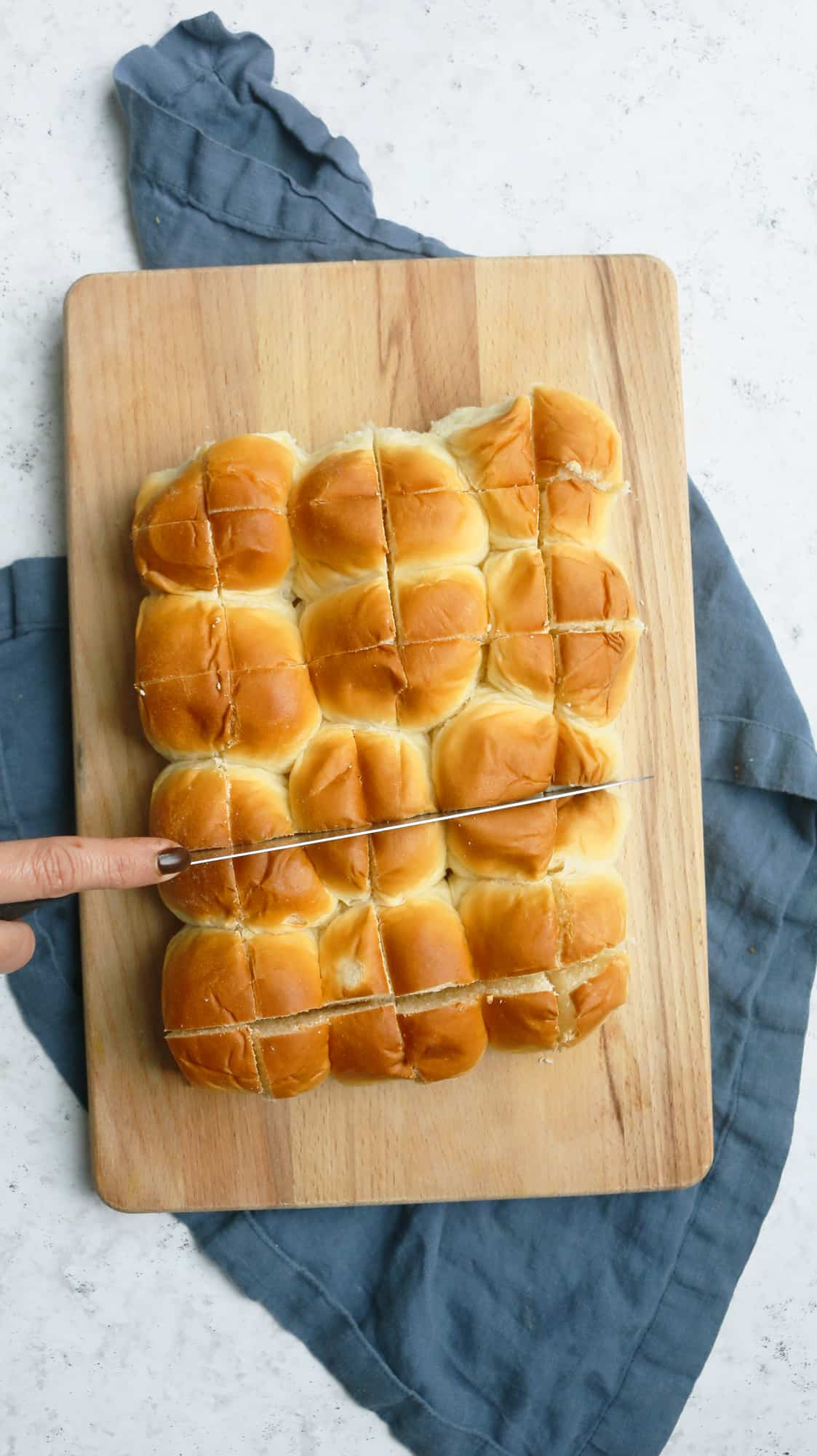 A hand cutting Hawaiian rolls crosswise which is placed on a cutting board over a turquoise cloth
