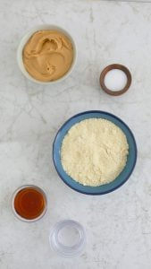 almond butter, salt, almond flour and maple syrup all displayed in individual bowls
