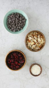 chocolate chips, sliced almonds and dried cranberries all displayed in individual bowls