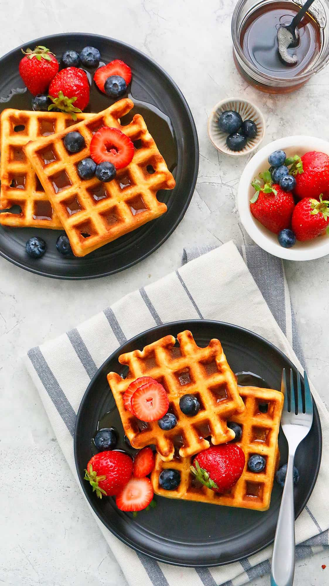 Belgian waffles from scratch topped with butter and fruits.