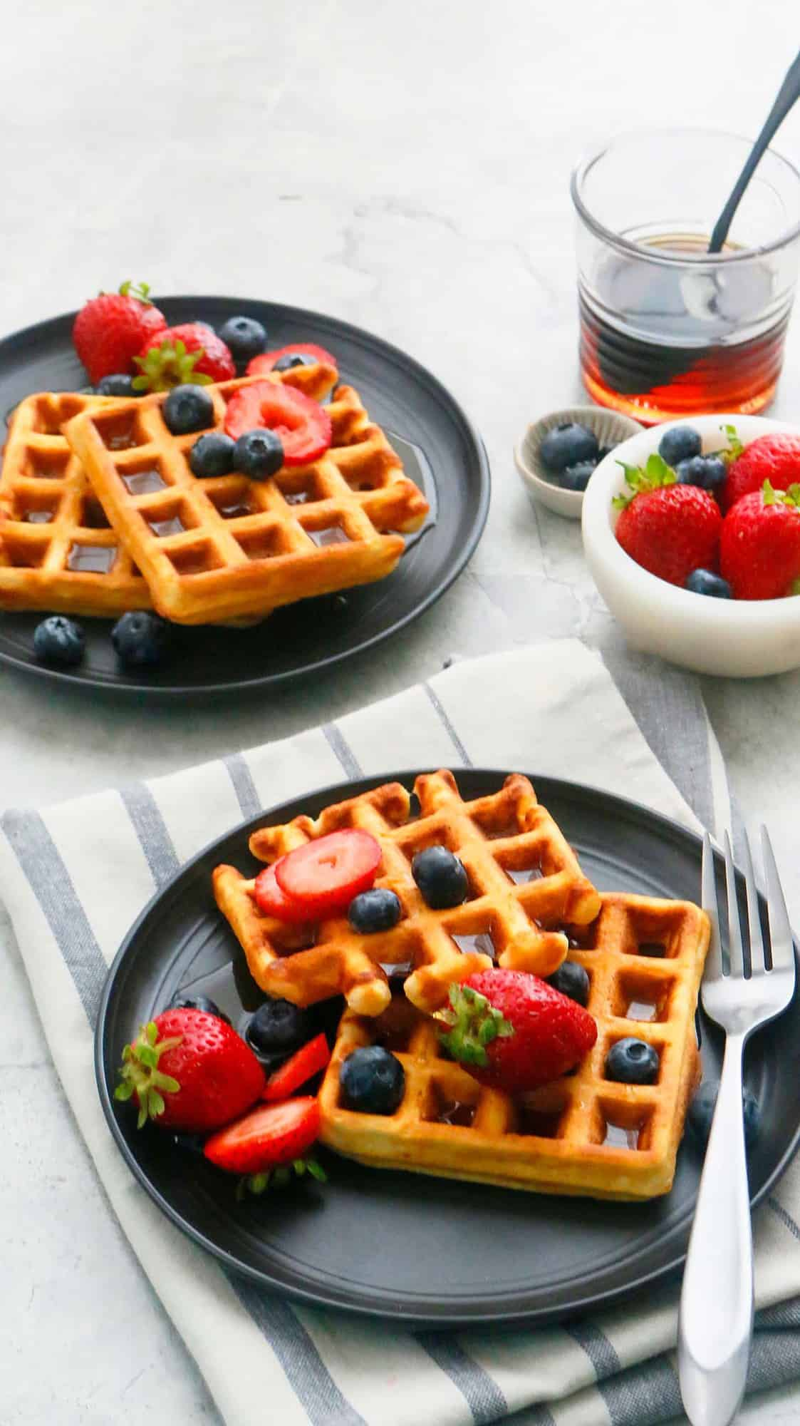 2 black plates with crispy Belgian Waffles with forks.