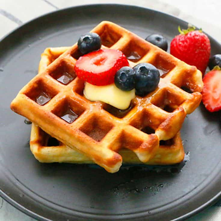 homemade Belgian waffles on a black plate topped with berries.