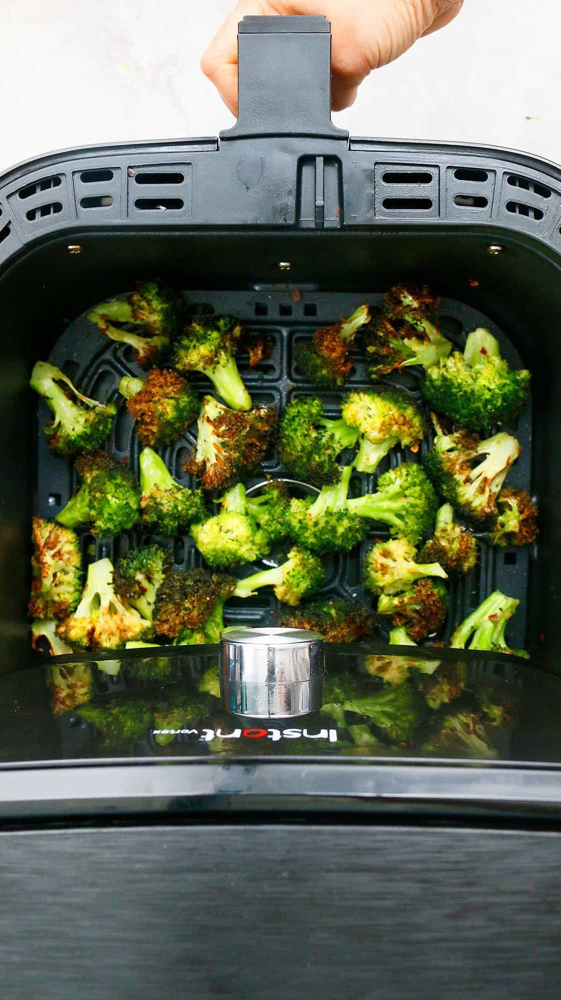 a hand pulling out an air fryer basket with crispy roasted broccoli