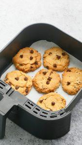 freshly baked chocolate chip cookies in an sir fryer basket