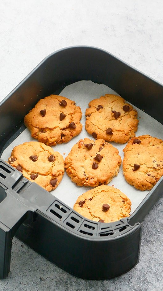 freshly baked chocolate chip cookies in an sir fryer basket