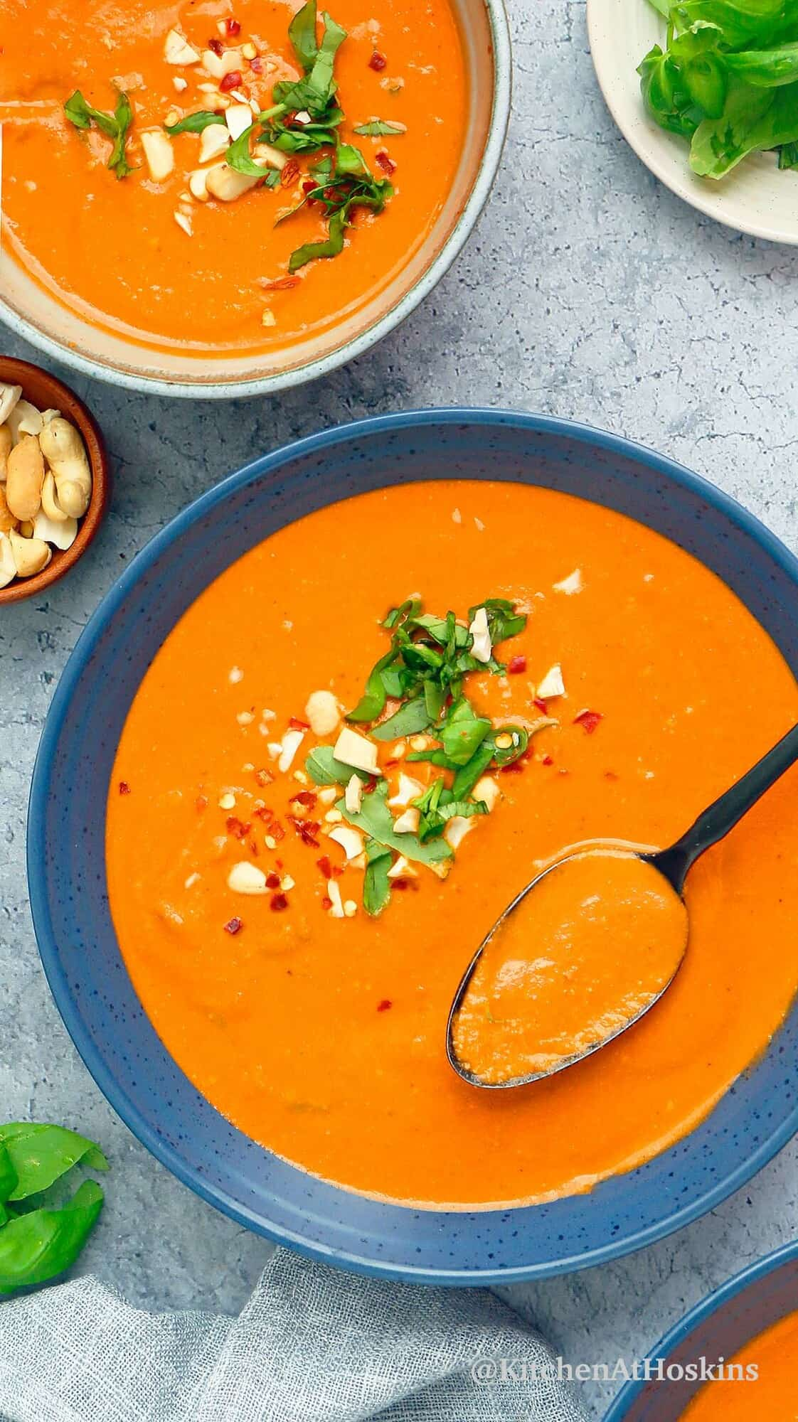 blue bowls with vegan tomato soup, topped with chopped basil and cashews.