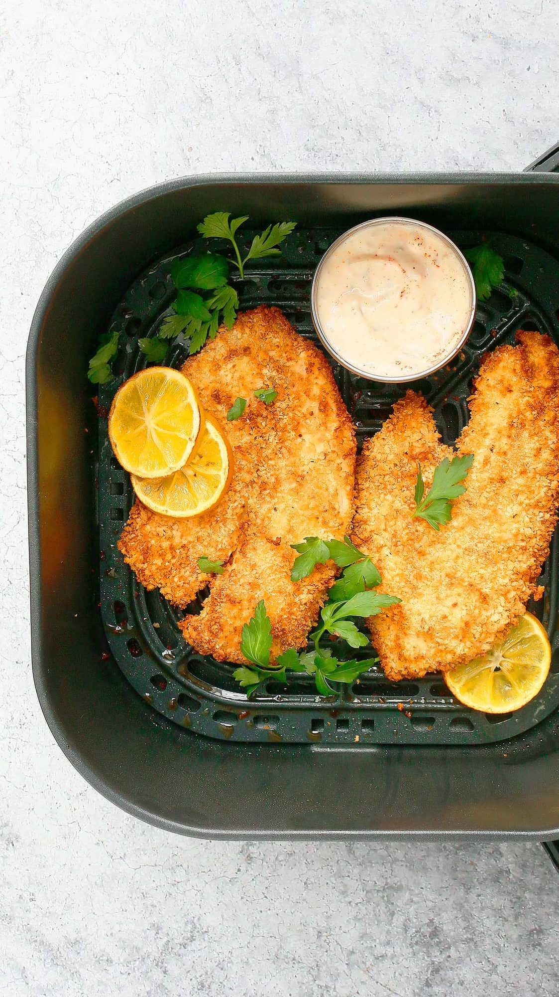 an air fryer basket with cooked tilapia along with tarter sauce