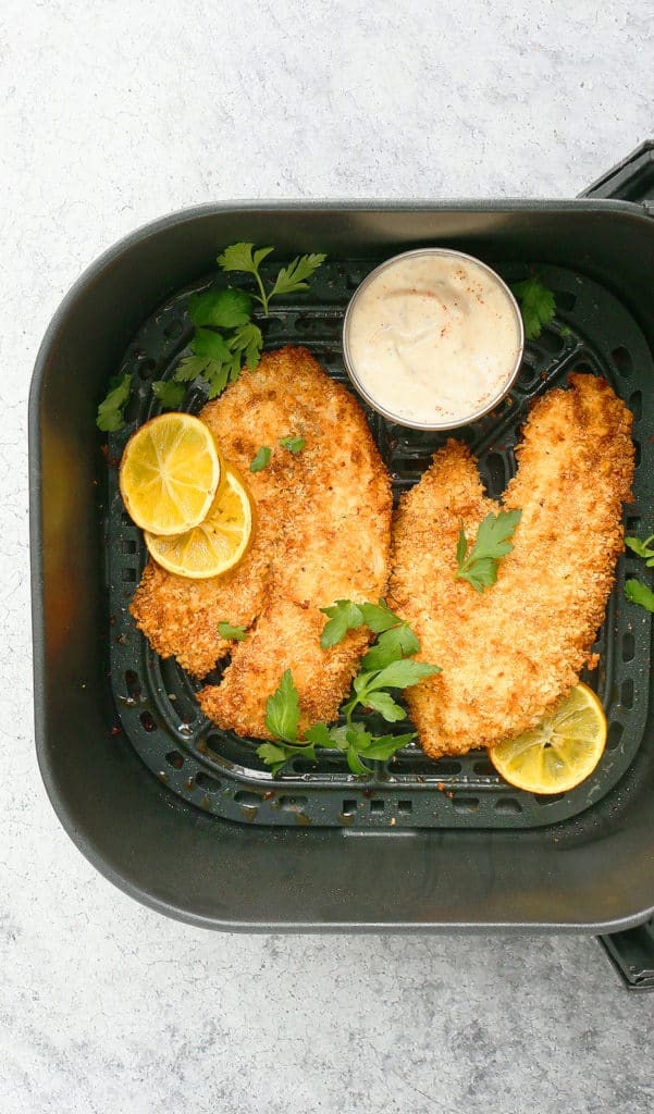 air fryer basket with tilapia with a side of sauce in a small bowl and garnished with parsley and lemons