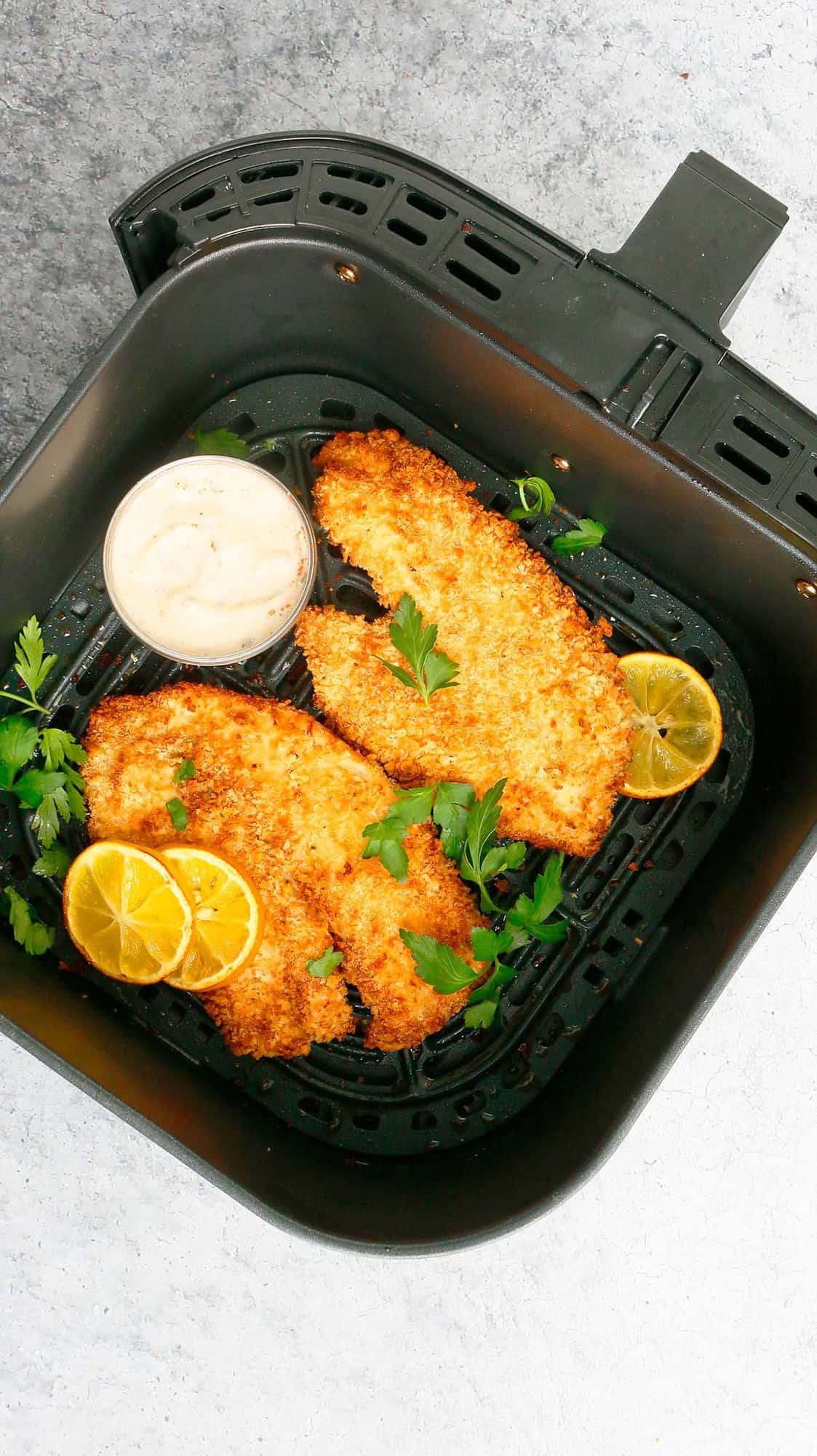 an air fryer basket with cooked tilapia garnished with lemon slices and parsley