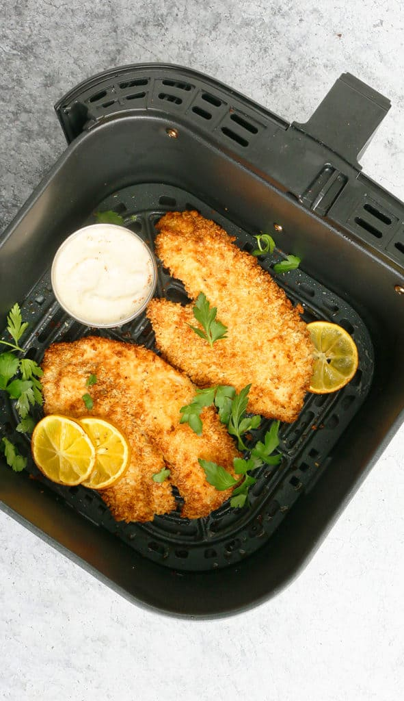 air fryer basket with crispy tilapia with a side of sauce in a small bowl and garnished with parsley and lemons