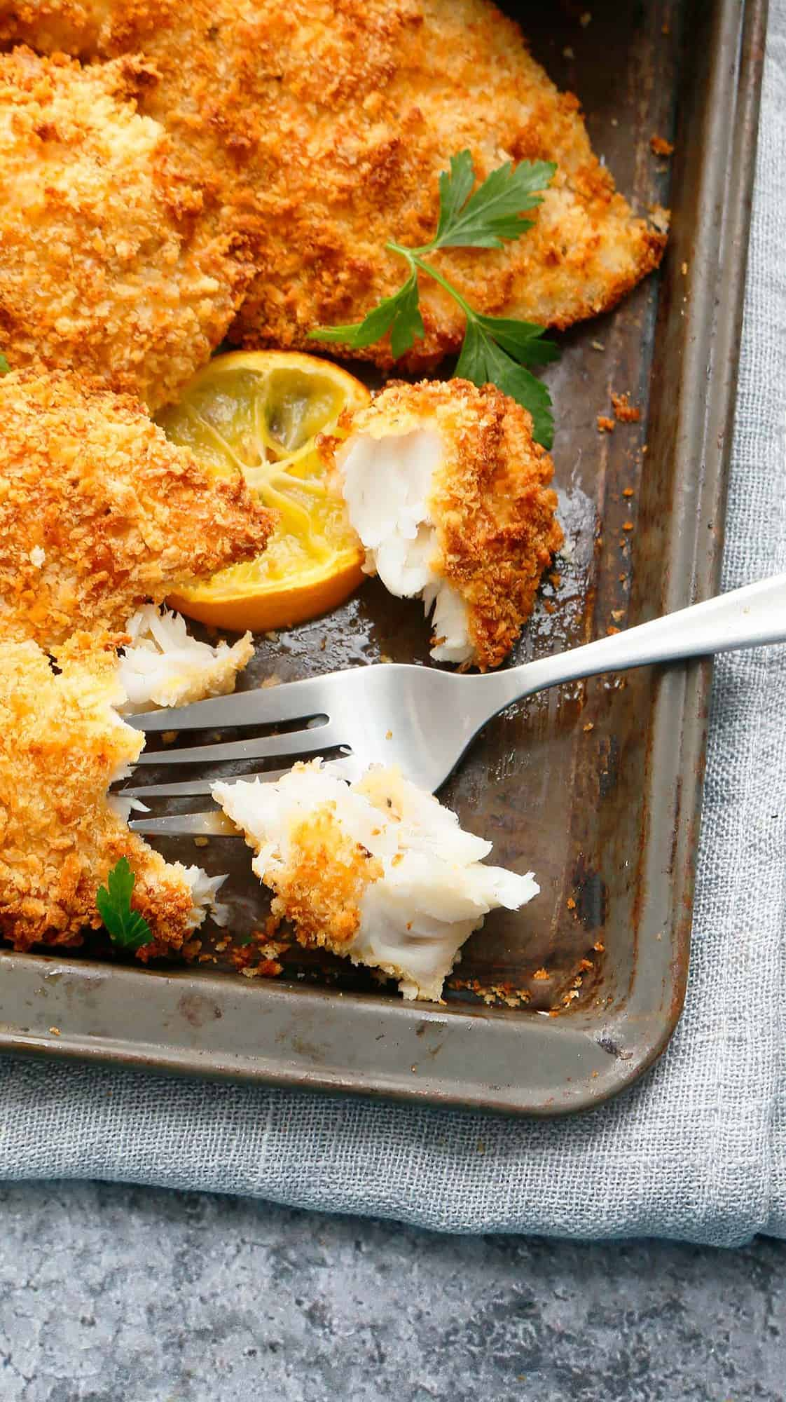 baking tray with crispy tilapia with one cut into chunks with a fork