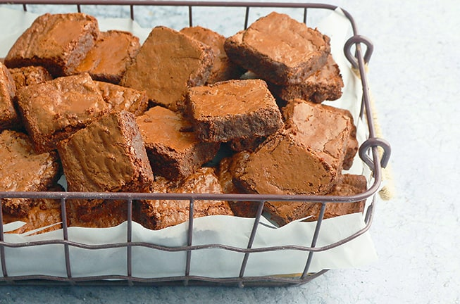 a metal basket lined with parchment paper with full of almond flour brownies