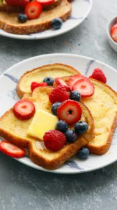 a plate with french toast topped with maple syrup and berries