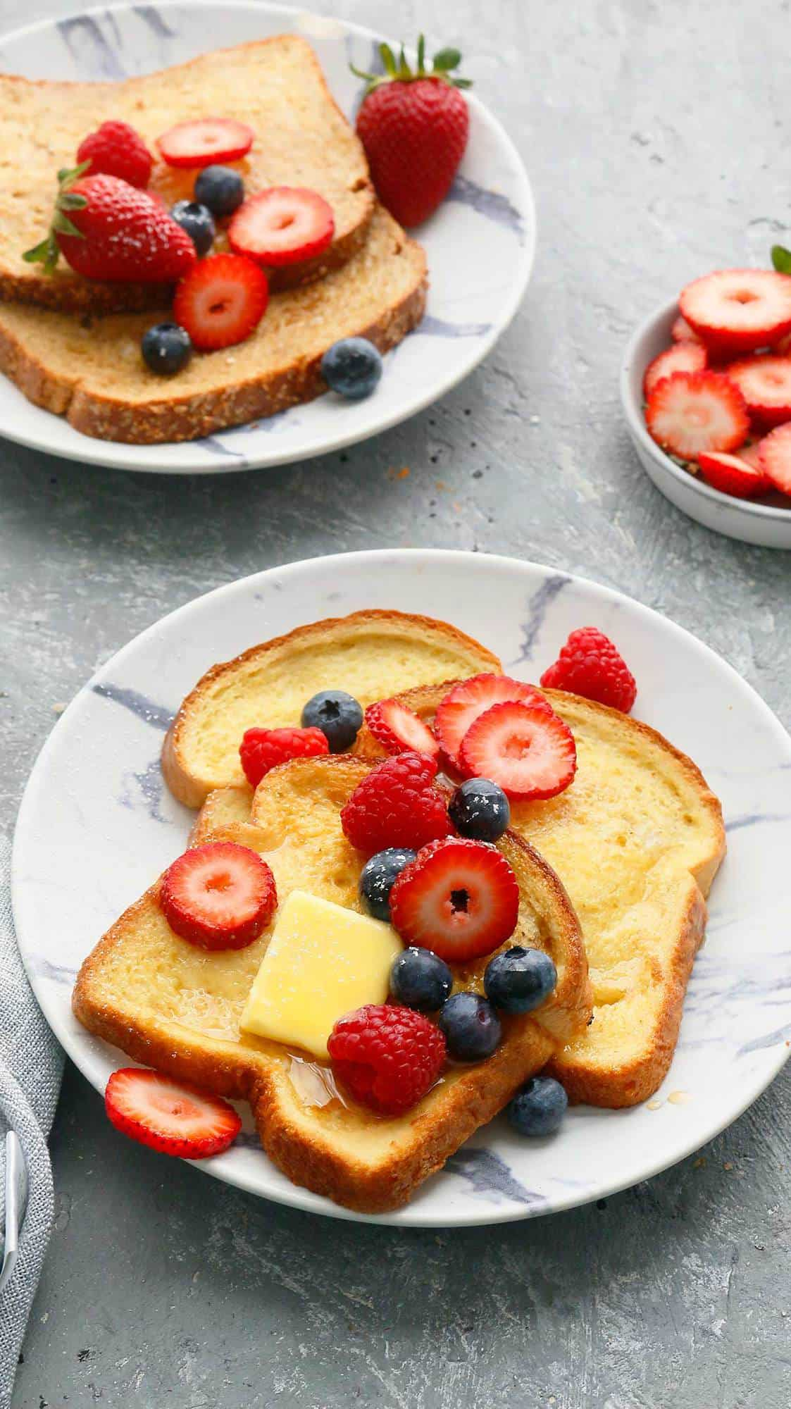 white plates with french toast in air fryer topped with butter and berries