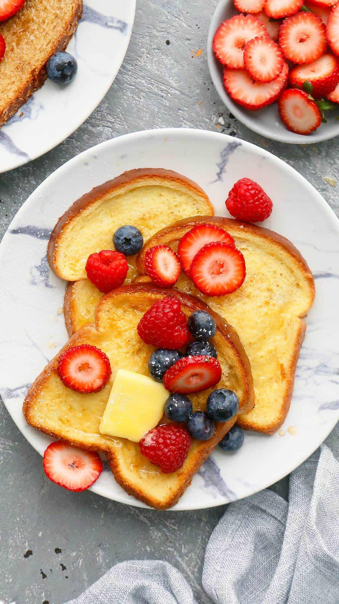 white and blue plates with toasts topped with butter and berries