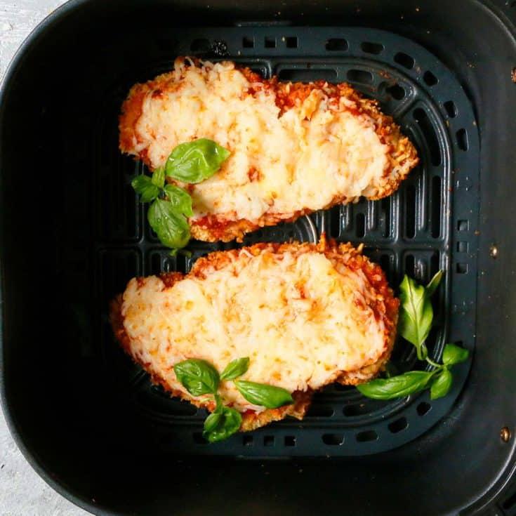 an air fryer basket with chicken parmesan