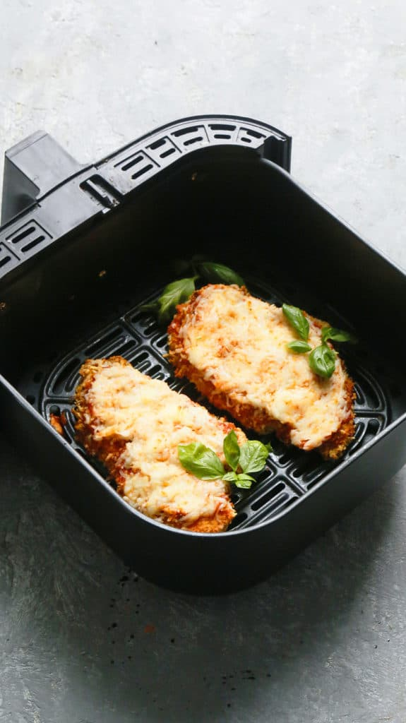 an air fryer basket with chicken parmesan garnished with fresh basil