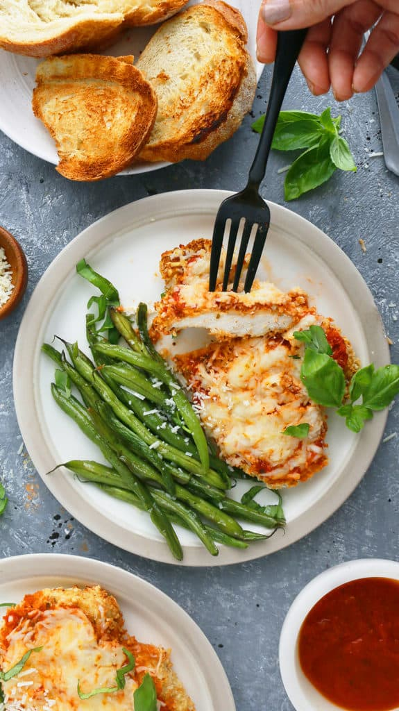 a black fork trying to take a bite off chicken parm in air fryer along with green beans, forks, toasted bread, fresh basil and marinara sauce