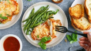 Chicken parm in air fryer recipe on white plates with a piece being grabbed by a fork.