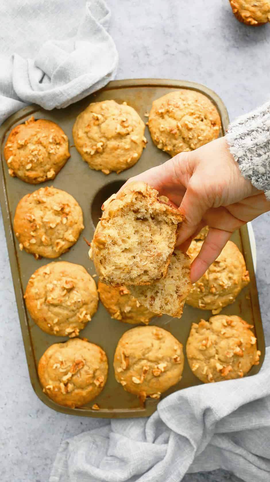 a hand holding half a banana muffin above a pan full of muffins