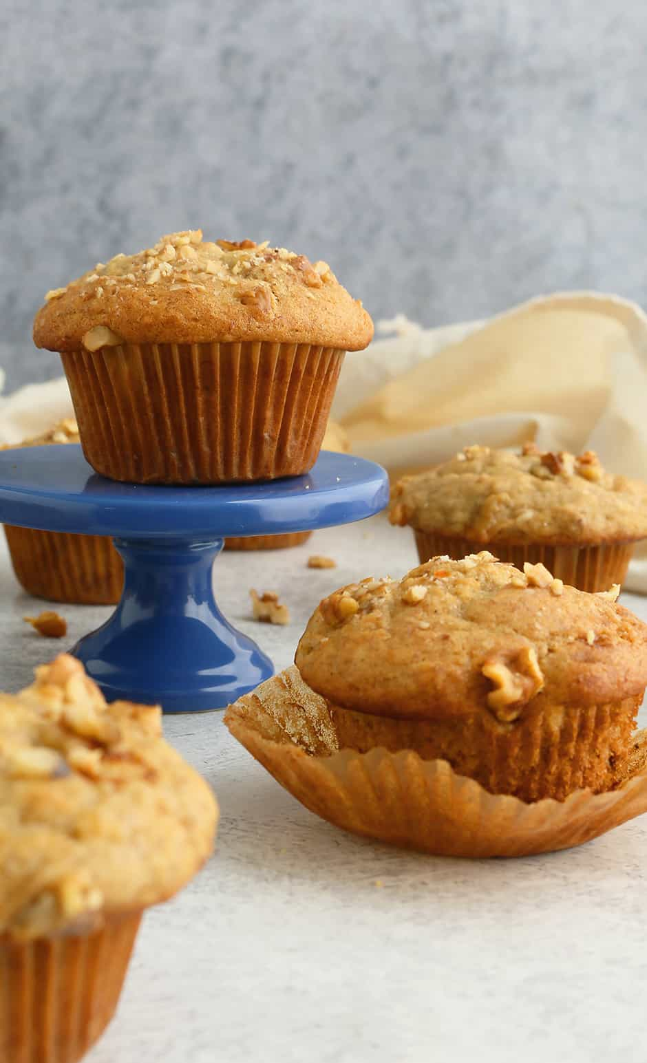 an eggless banana muffin placed on a blue cupcake stand along with more muffins