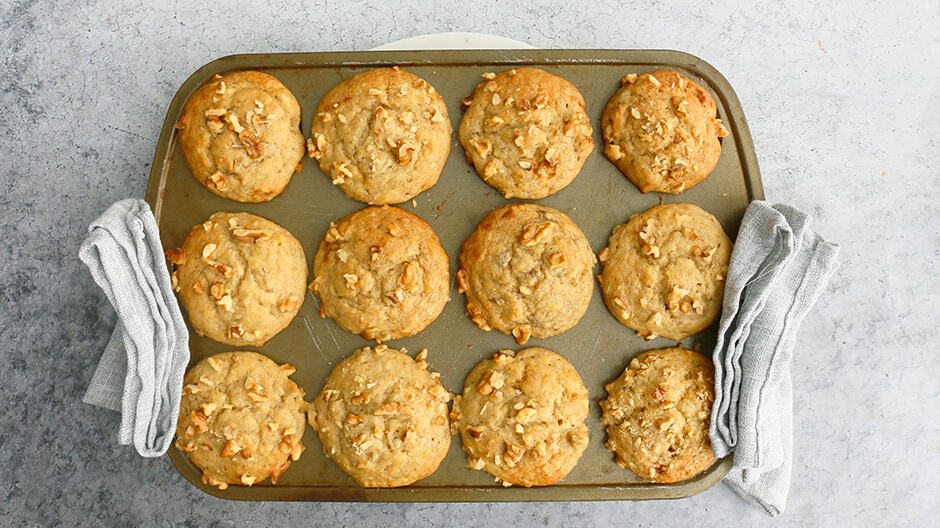 a muffin pan with freshly baked eggless banana muffins with grey towels on either side