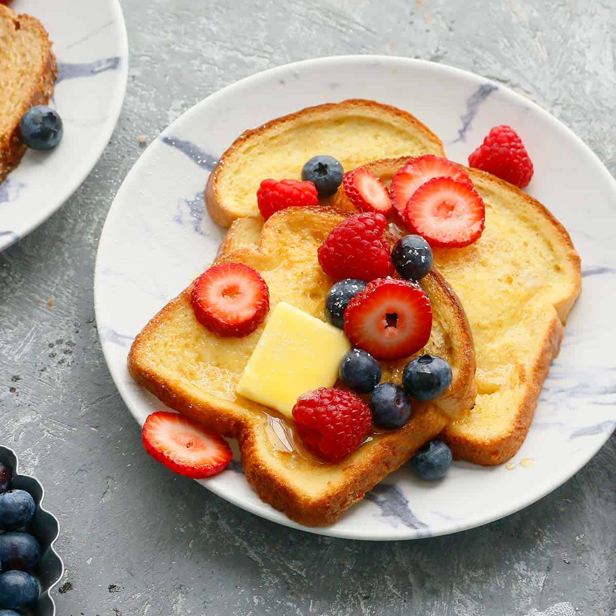white plates with air fried french toast topped with butter and berries