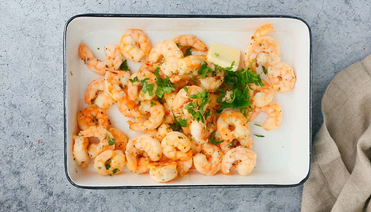 a rectangle tray with cooked shrimp, butter and parsley