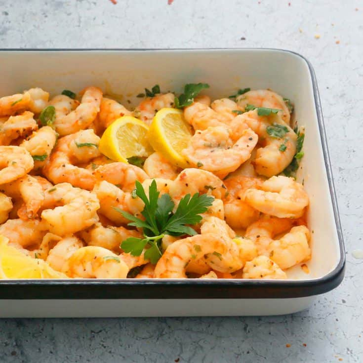 air fryer garlic shrimp placed in a white platter garnished with parsley and lemon wedges