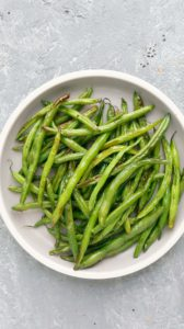 white rimmed plate with cooked green beans