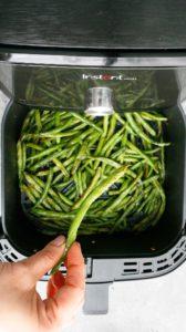 a hand holding a green bean above an open air fryer full of cooked green beans