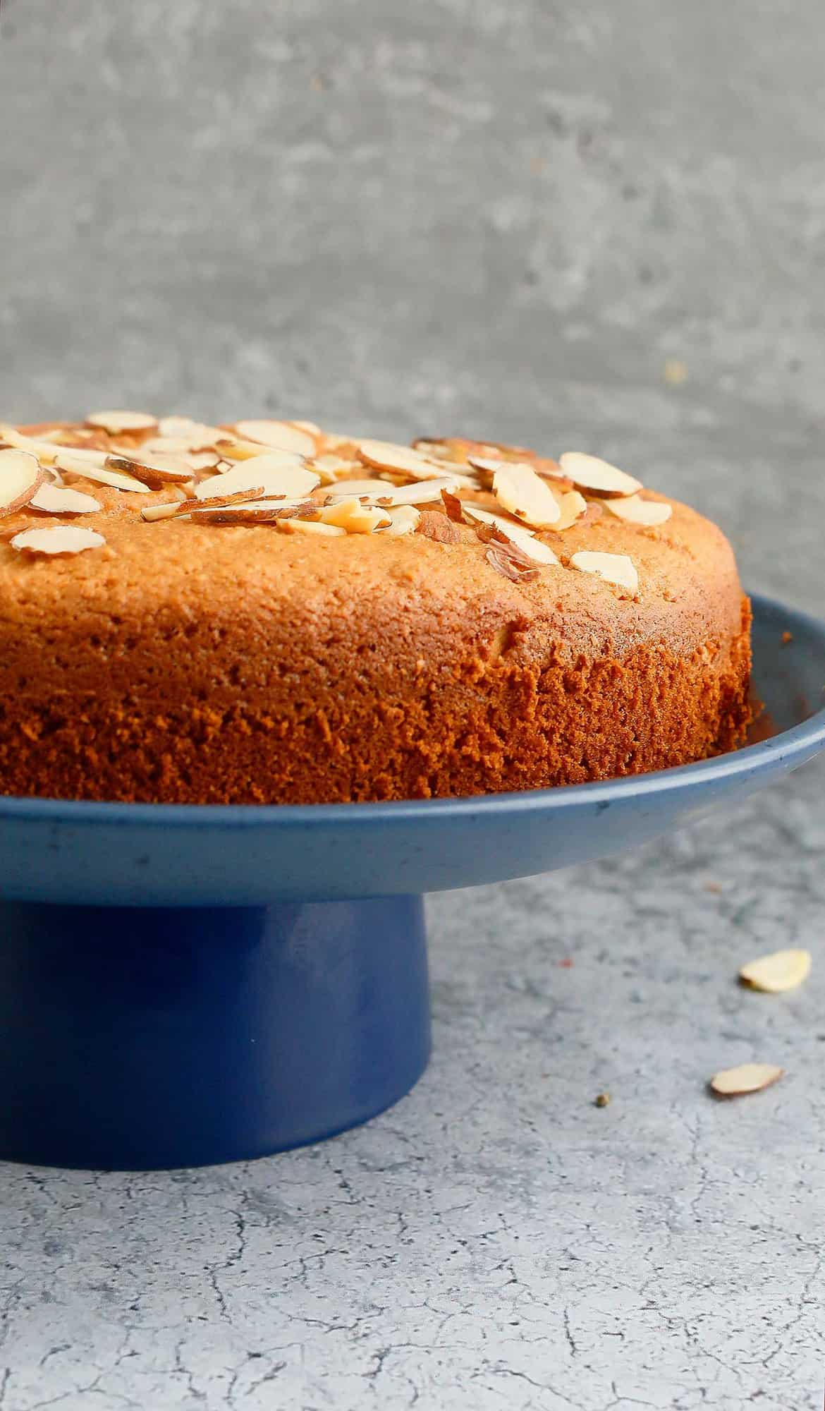 Gluten free almond cake placed on a blue cake stand