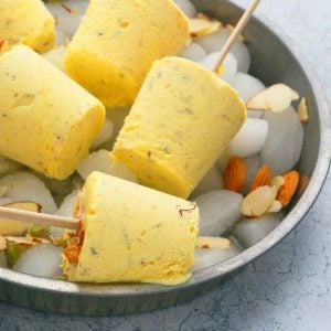Badam Kulfi placed on a tray filled with ice
