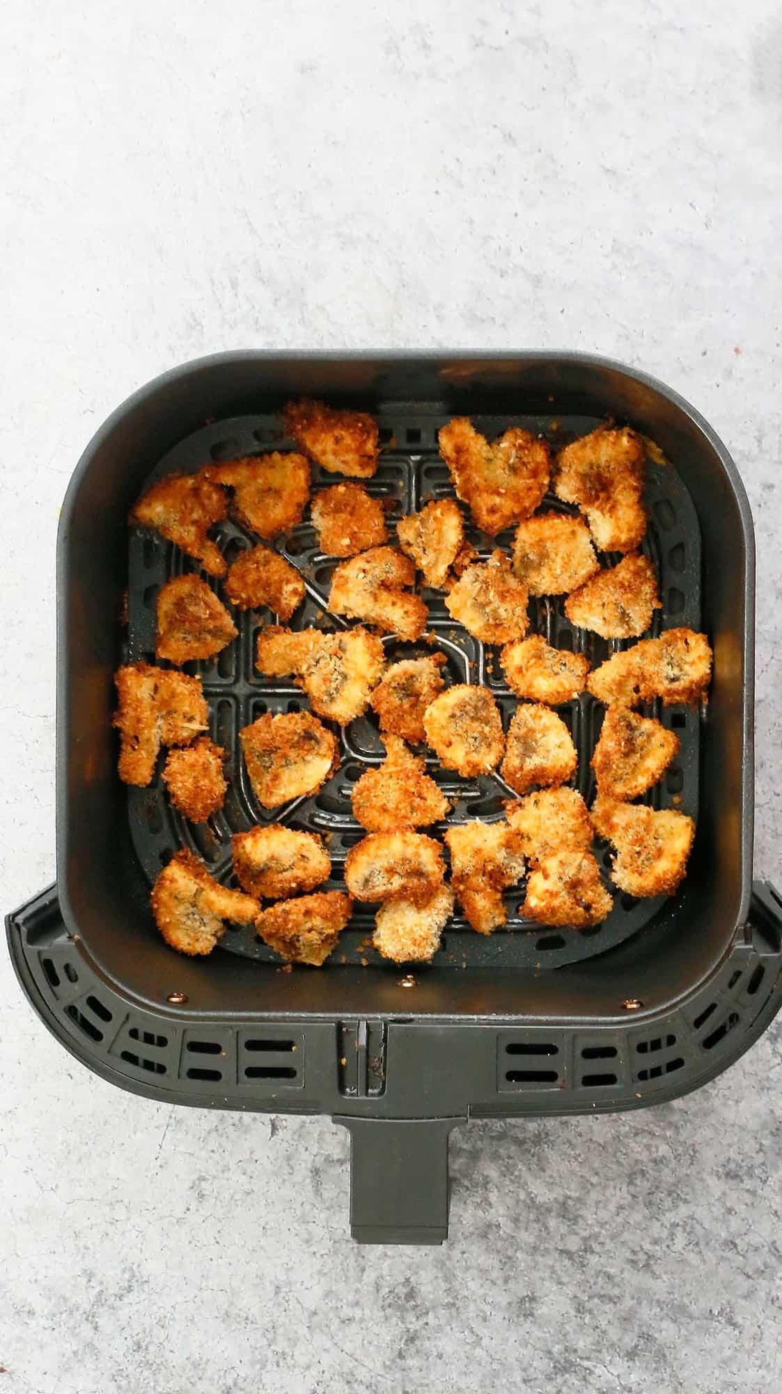 an air fryer basket with crispy breaded mushrooms