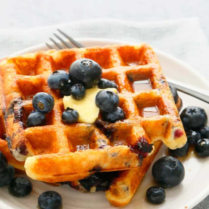 homemade blueberry waffles on a white plate topped with butter, maple syrup and more blueberries