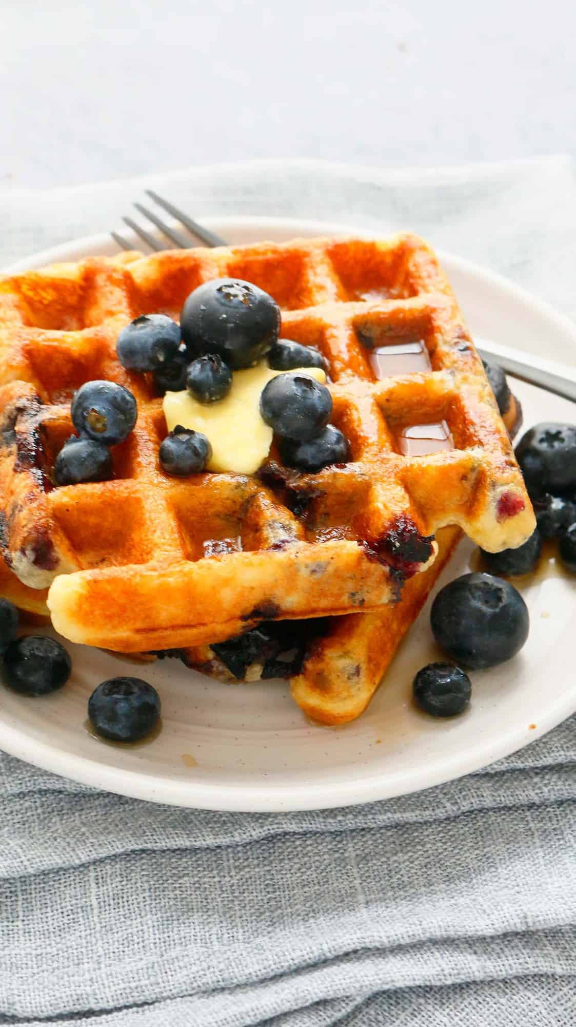 2 blueberry waffles on a white plate, topped with butter, maple syrup and more fresh blueberries