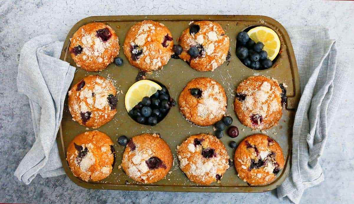 a muffin pan with baked lemon blueberry muffins along with folded grey kitchen towels on both sides