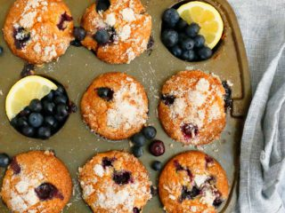 lemon blueberry muffins on a muffin pan garnished with blueberries and lemon slices