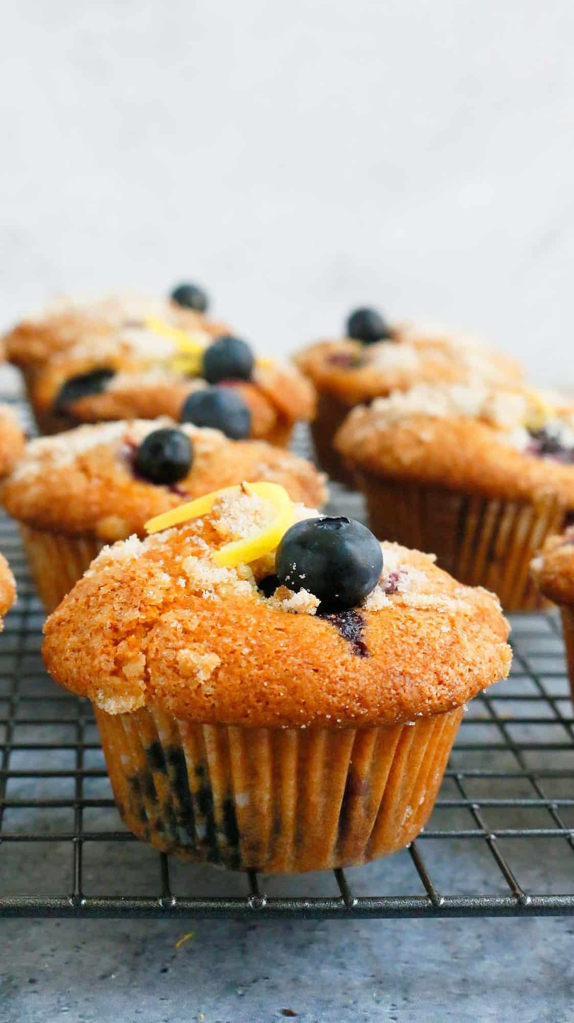 muffins garnished with blueberries & lemon zest placed on a wire rack
