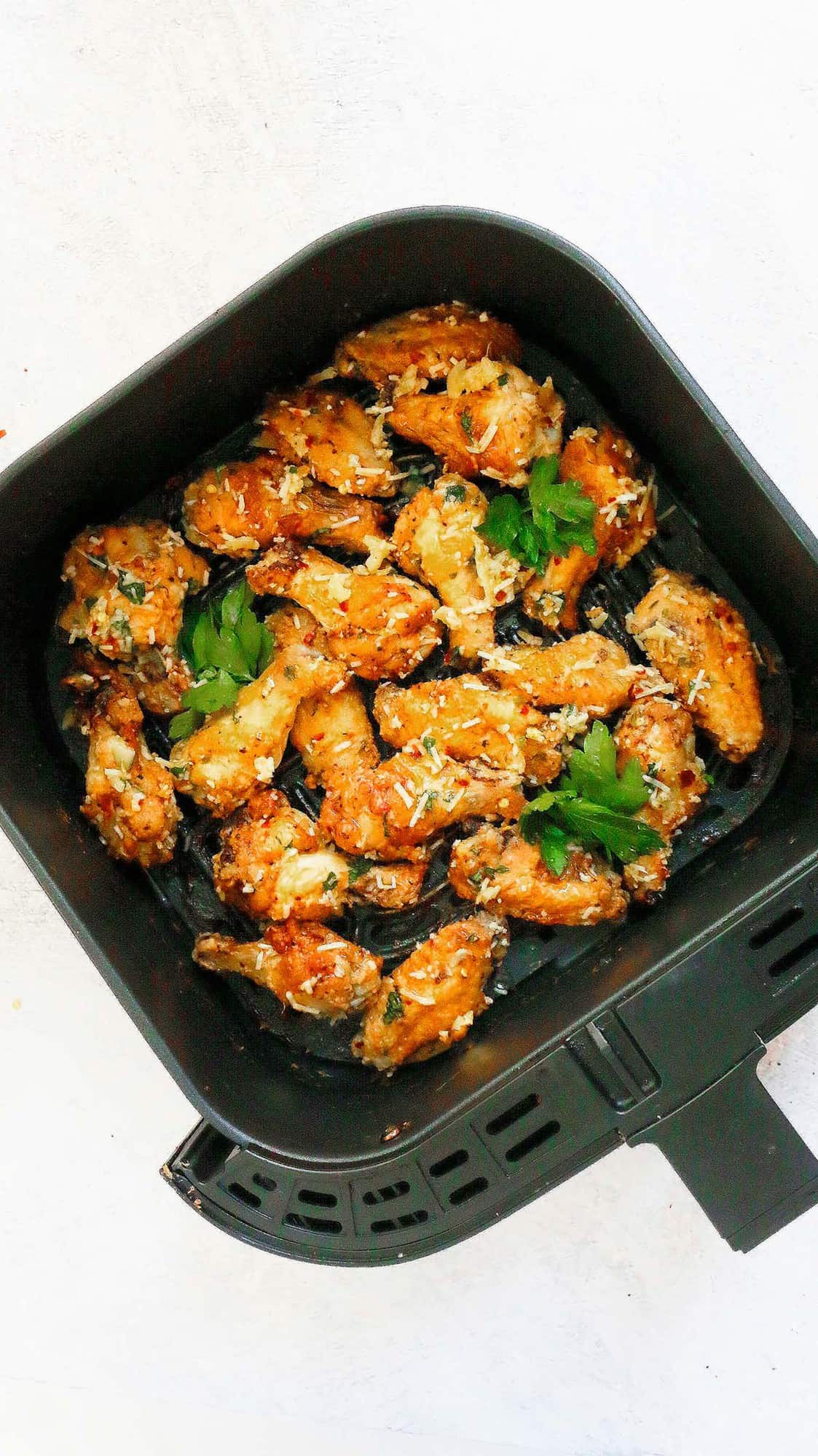 air fryer basket with cooked garlic parmesan wings garnished with fresh parsley