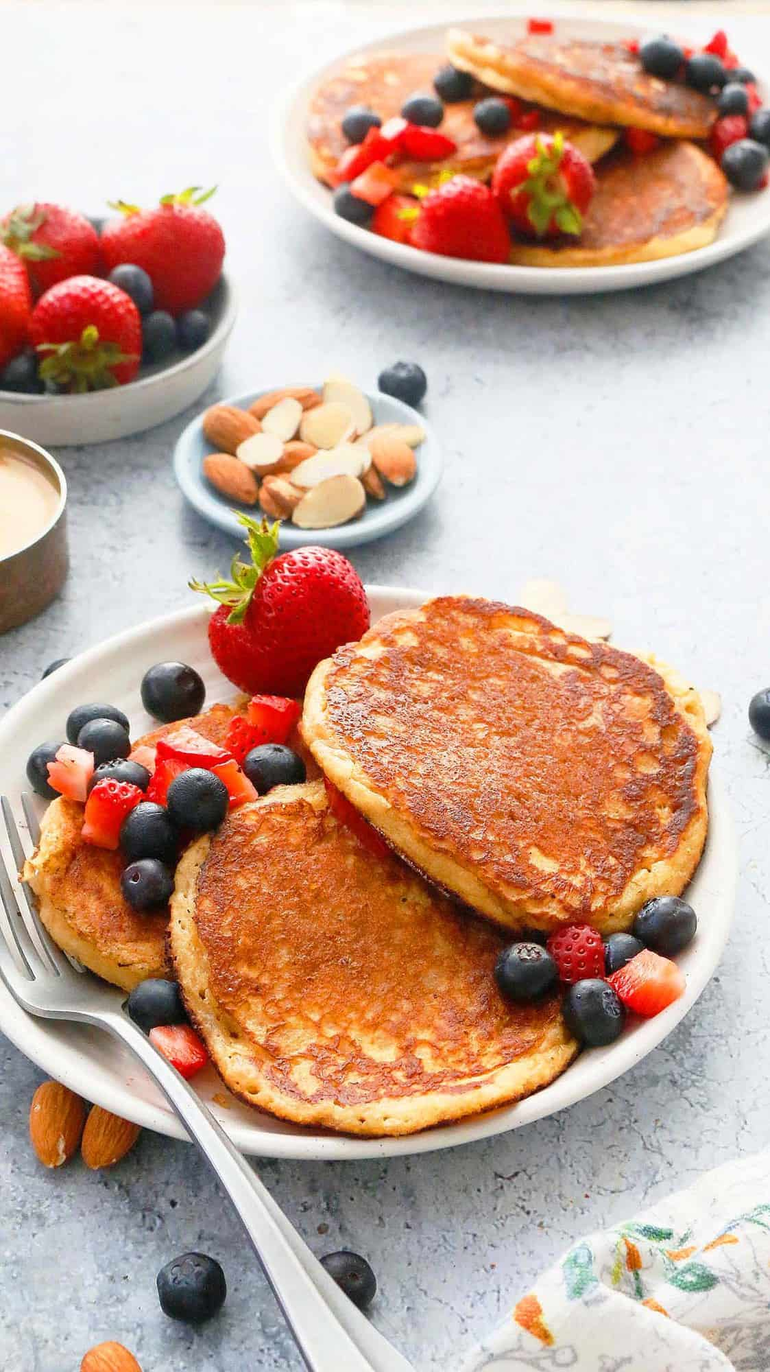 white plates with almond buttermilk pancakes and fresh berries