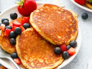 white plate with 3 almond pancakes along with a fork and fresh berries