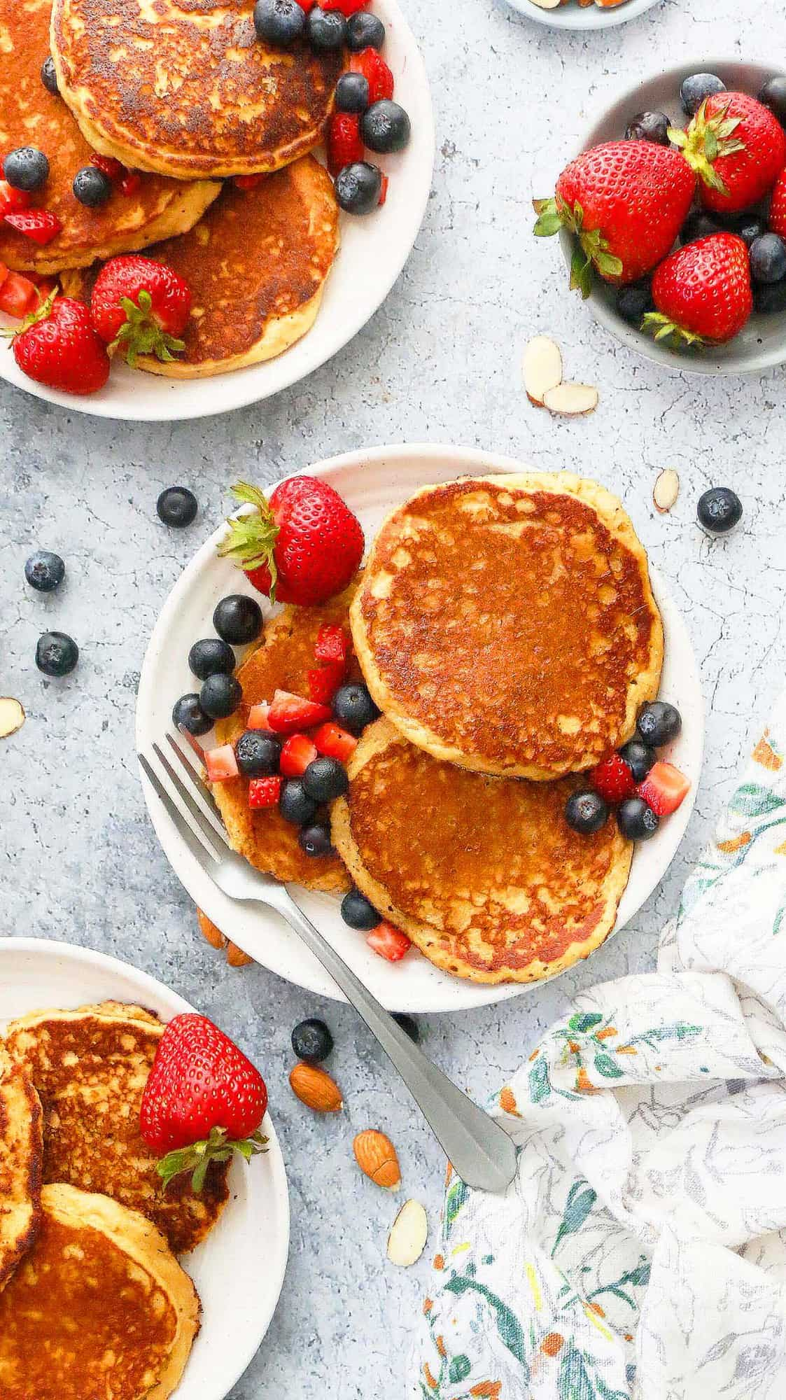 3 white plates with almond butter almond flour pancakes along with fresh berries